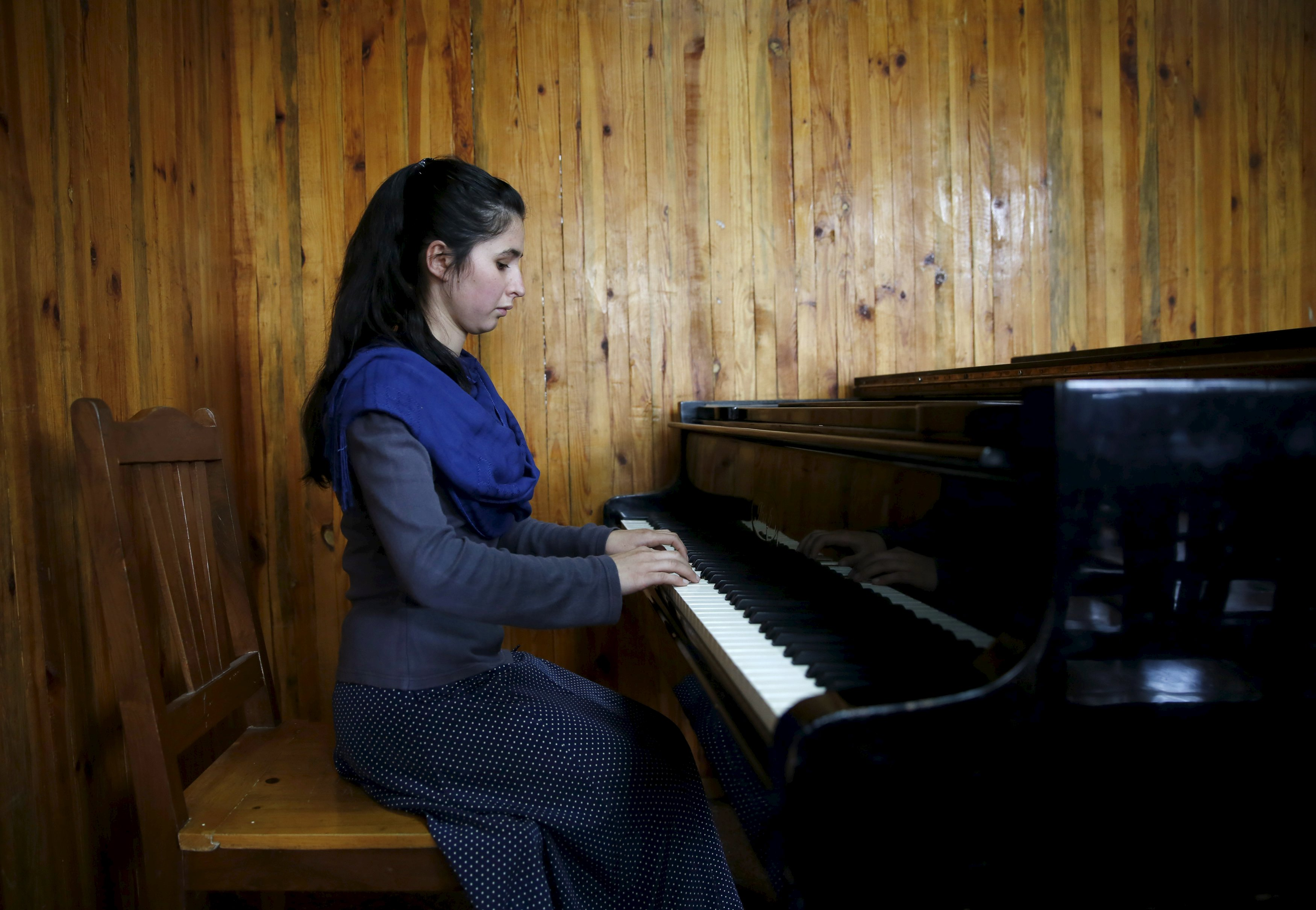 """Negin Ekhpulwak, leader of the Zohra orchestra, an ensemble of 35 women, practises on a piano at Afghanistan's National Institute of Music, in Kabul, Afghanistan April 9, 2016. Playing instruments was banned under Taliban rule in Afghanistan, and even today, many conservative Muslims frown on most forms of music. Living in an orphanage in the capital, Kabul, 19-year-old Negin leads an ensemble of 35 women that plays both Western and Afghan musical instruments. In a country notorious internationally for harsh restrictions on women in most areas of life, Negin's story highlights a double challenge. REUTERS/Ahmad Masood SEARCH """"ORCHESTRA KABUL"""" FOR THIS STORY. SEARCH """"THE WIDER IMAGE"""" FOR ALL STORIES TPX IMAGES OF THE DAY"""