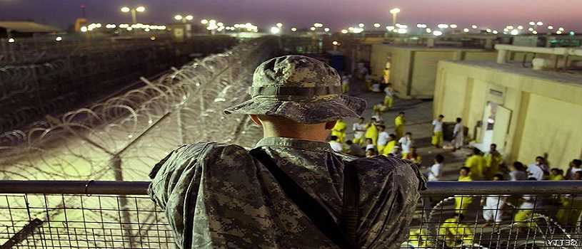 BAGHDAD, IRAQ - SEPTEMBER 19: A U.S. Army soldier watches Iraqi detainees at the Camp Cropper detention center September 19, 2007 in Baghdad, Iraq. U.S. forces have a total of about 25,000 detainees in several centers in Iraq, up from only about 14,000 before the American troops surge this year. The detainee population includes insurgents from all anti-coalition groups in Iraq, Al Qaeda foreign fighters, criminals and many innocent Iraqis caught up in U.S. military raids. Military officials say they have instituted a new review process to more quickly identify the innocent detainees for release.  (Photo by John Moore/Getty Images)